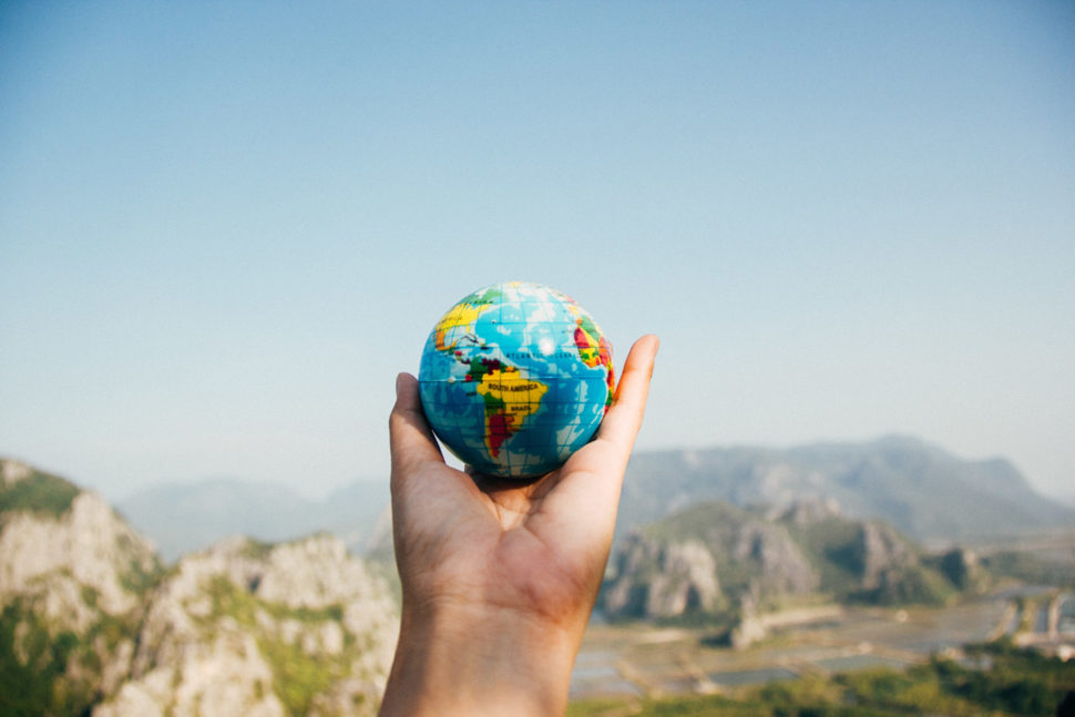 Hand holding a small globe of our world