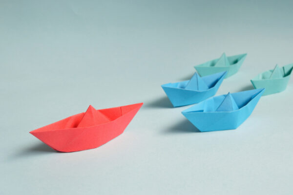 Red paper boat with 3 blue paper boats trailing it.