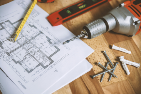 Power tools & architectural plan laid out on wooden table.